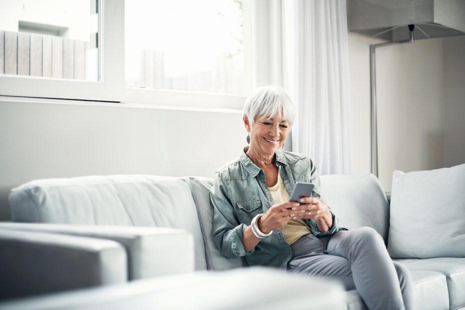 Ältere Frau mit Smartphone auf dem Sofa